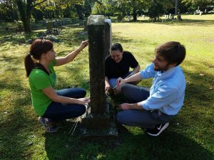 Staff of Historic St. Luke's working together to clean an historic gravestone.